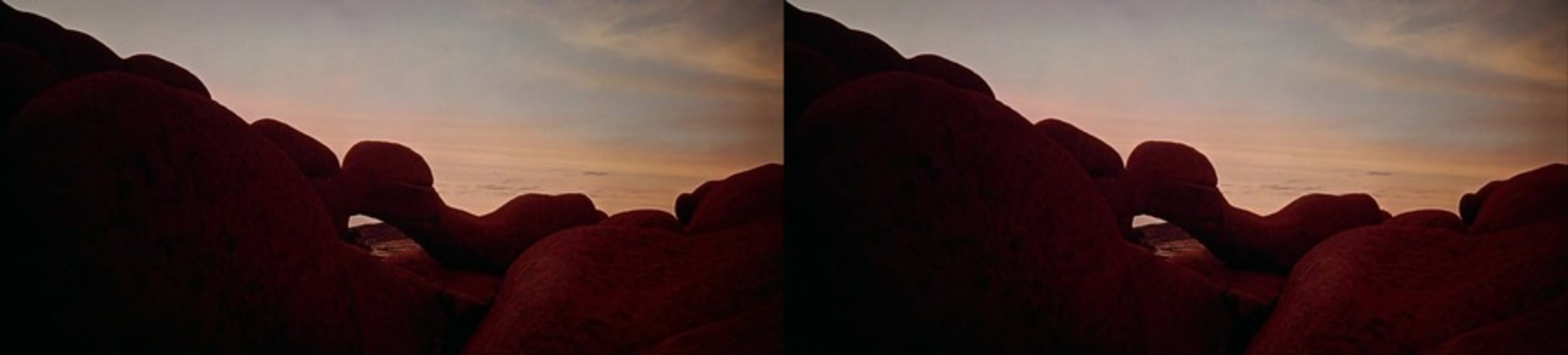 The image is clearly divided down the middle, creating a left side and a right side. Left side: a rock formation with rosy clouds and blue sky behind it. Right side: same as the left side.