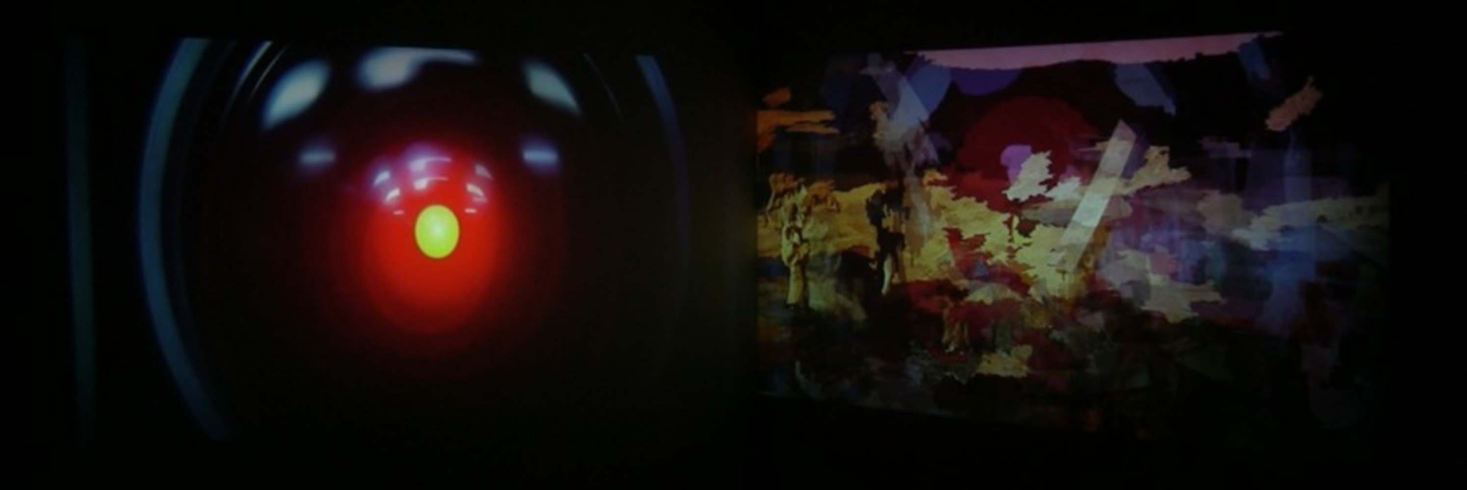 "The image is clearly divided down the middle, creating a left side and a right side. Left side: a bright yellow light surrounded by a glowing red halo of light, both set in the center of a large, shiny black circle. It is a mechanical ""eye."" Right side: splotches of color that do not clearly represent specific scenes, but some warm colors and textures of desert landscape are emphasized. There are concentric circles of yellow and red with some subtle blue halos around them. These circles very slightly resemble the mechanical eye on the left."
