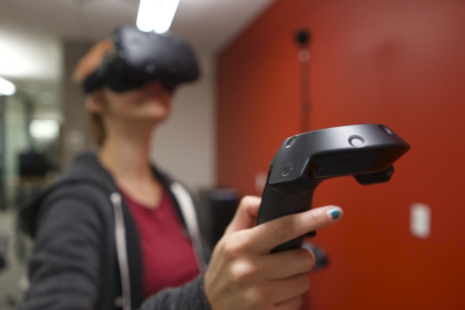 A person wearing a virtual reality headset holds a controller at arm's length.